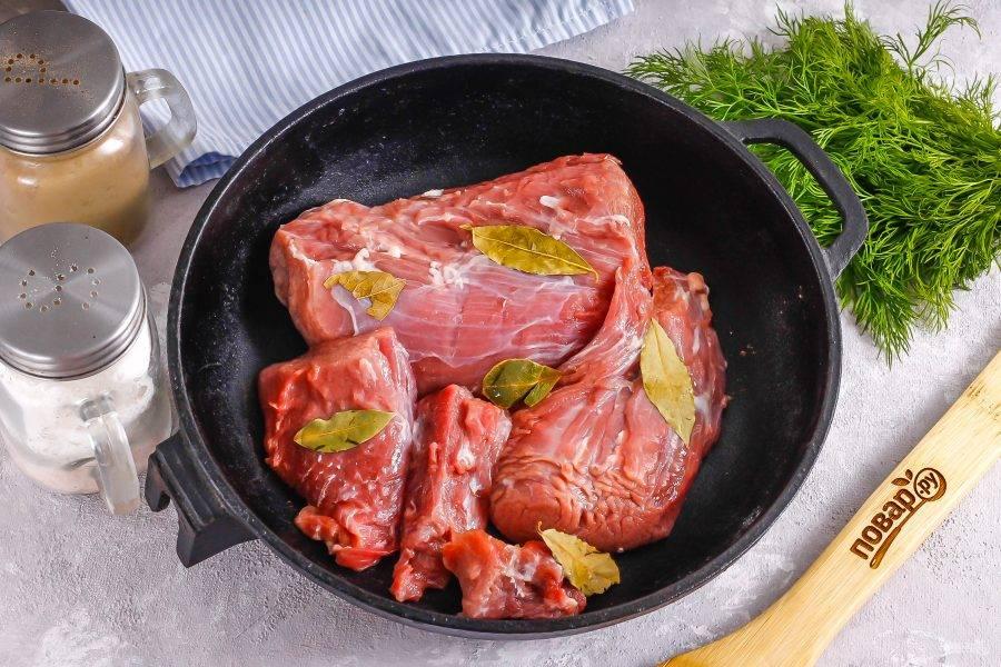 Мясо промойте в воде и срежьте с него все жилы и пленки. Выложите в форму для запекания, присыпьте солью, добавьте лавровые листья.