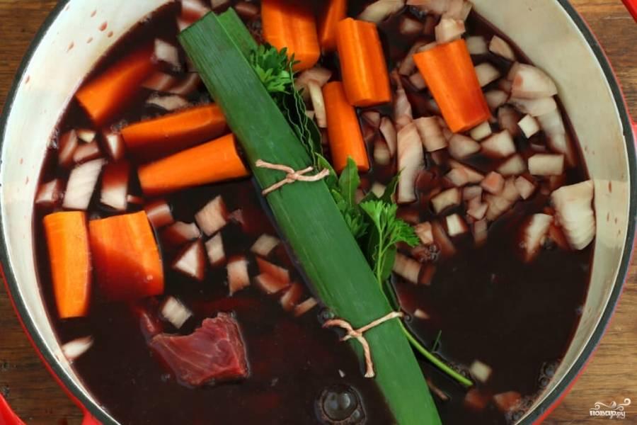 Лук-порей и петрушку свяжите в один пучок при помощи натуральных ниток. Эта зелень нужна лишь для аромата, потом её нужно будет удалить. Репчатый лук и морковь порежьте произвольными кусочками и сложите в кастрюлю. Туда же выложите мясо и пучок зелени. Всё это залейте вином, накройте крышкой и отправьте в холодильник мариноваться на 24 часа.