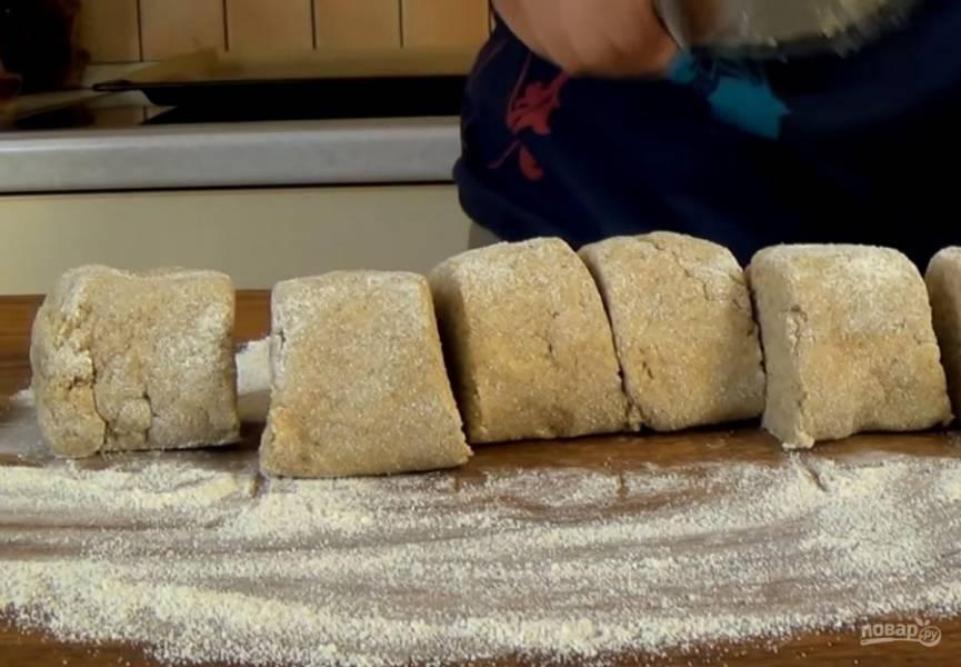 2. Тесто накройте пищевой пленкой и оставьте при комнатной температуре на 20 минут. Доску обильно присыпьте мукой, выложите тесто, сформируйте жгут и разрежьте его на шесть частей.