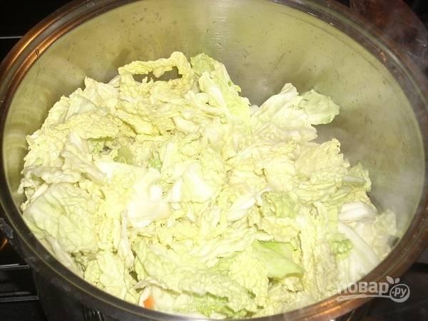 Добавляем нарезанную капусту. Можно нарезать тонкой соломкой, а можно и пошире. Добавим еще стакан горячей воды. Потушим минут 5.