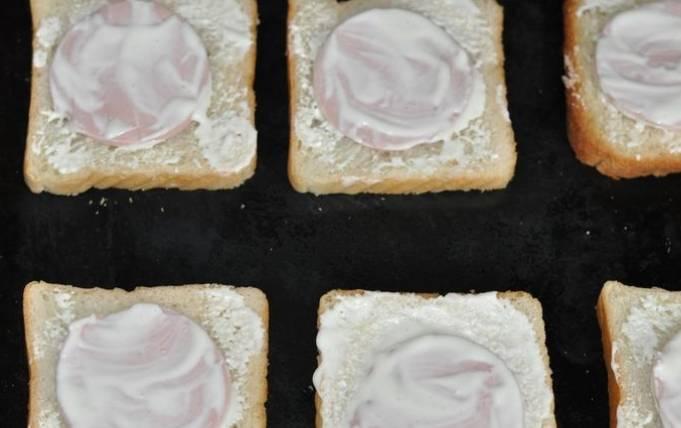 Кладем целые кусочки хлеба на противень, сверху выкладываем колбасу, добавляем чуть майонеза, соль и перец.