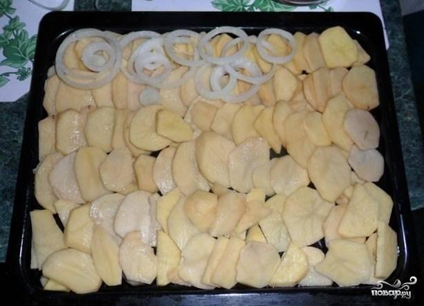 5. Лук очищаем и нарезаем тоненькими полукольцами или кольцами. Выкладываем его на картофель равномерным слоем.