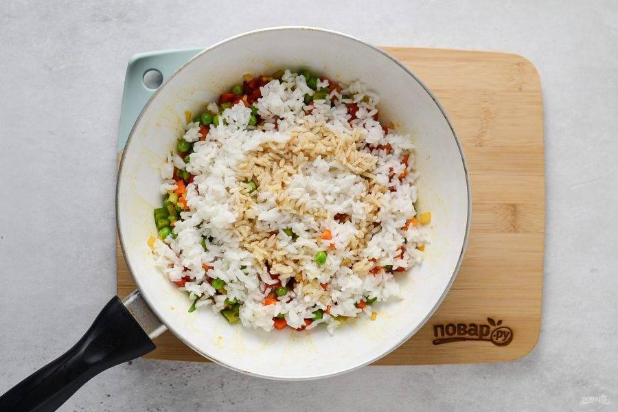 Добавьте отваренный рис и сахар, влейте соевый соус. Перемешайте все и обжарьте до румяного цвета риса.