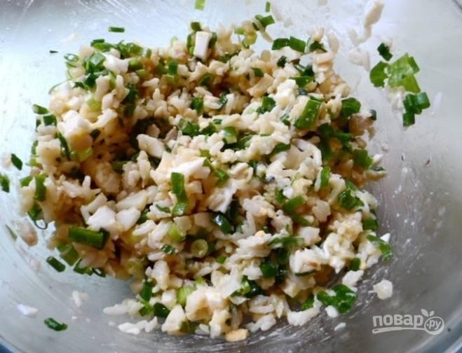 3. Извлекаем лишние кости и разделяем кусочки рыбы на части. Можно совсем измельчить, но это также по вкусу. Смешиваем отварной рис с зеленью, яйцами и консервами. У нас получилась начинка.