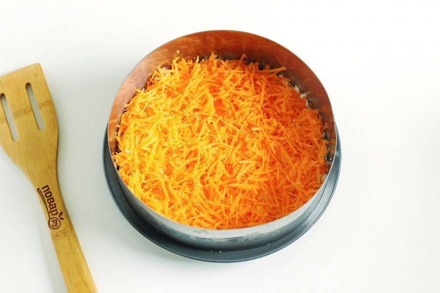 Сырую морковь очистите, нашинкуйте на средней или мелкой терке. Примерно половину тертой моркови выложите на белок. Сверху моркови сделайте сетку из майонеза.