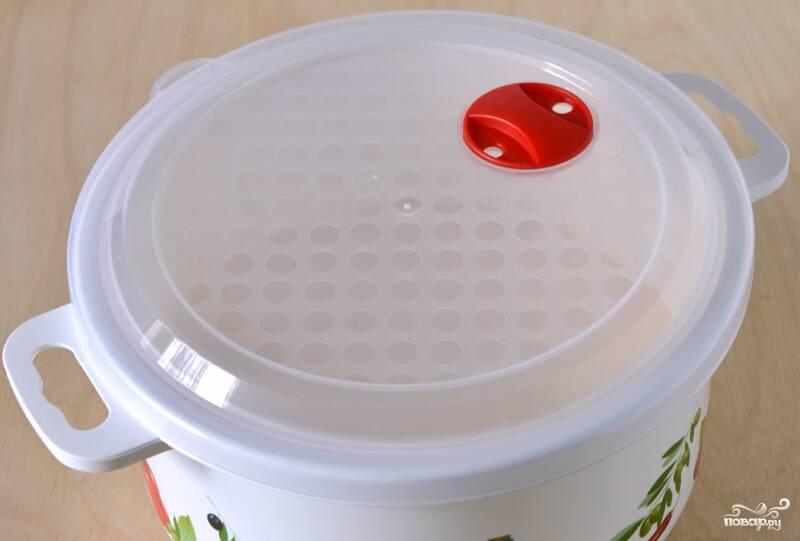 Форму для микроволновки смажьте маслом. Выложите в неё творожную смесь и закройте крышкой. Откройте клапан. Можно просто немного приоткрыть крышку.