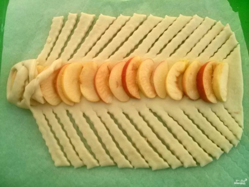 Ножом сделайте косые параллельные надрезы от яблок к краям теста. Начните заплетать полоски, чередуя с каждой стороны.