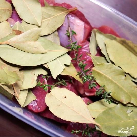 В миску кладем кусочки оленины, туда же добавляем лавровый лист, свежий тимьян, заливаем все это дело вином. Отправляем в холодильник на 12 часов - пускай маринуется.