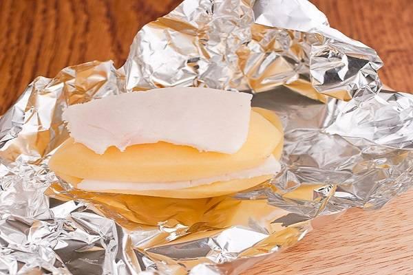 3. Листик фольги разверните, выложите на него половинку картофеля, а сверху - сало. Затем — вторую половинку и еще ломтик сала. Аккуратно заверните фольгу, чтобы в процессе запекания жир не вытекал.