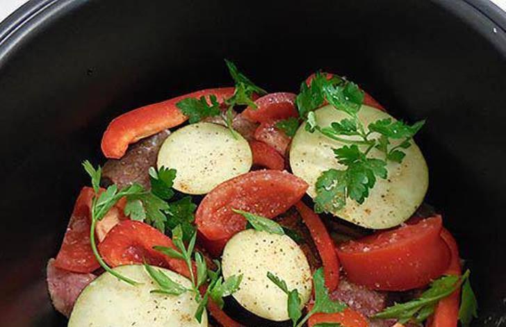 Выложите оставшиеся овощи – перец, вторую половину помидор и баклажан.  Посыпьте свежей зеленью, еще посолите и посыпьте приправой. Воды не добавляйте, в процессе готовки выделится достаточно сока.