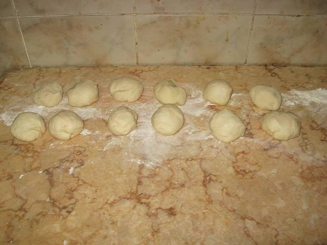 1. Из указанных ингредиентов замесим тесто. Оставим его, чтобы дрожжи подействовали, а тесто поднялось хотя бы в полтора раза. Обминаем тесто, затем формируем из него одинаковые кусочки.