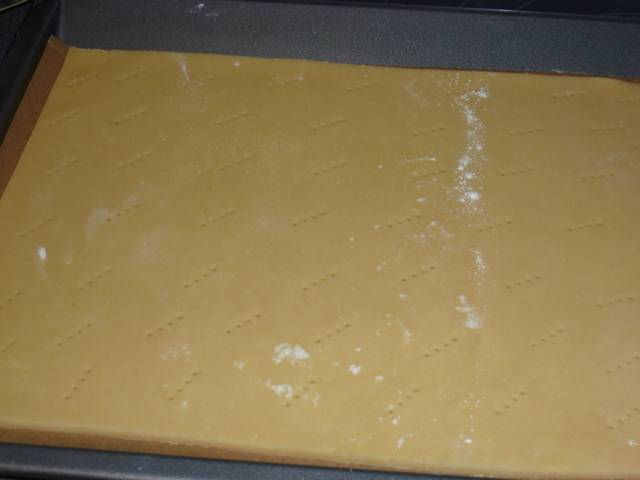 Достаем тесто из холодильника, раскатываем в пласт толщиной 3-5 мм. Ставим в разогретую до 180 градусов духовку на 6 минут. Тесто наколоть вилкой.