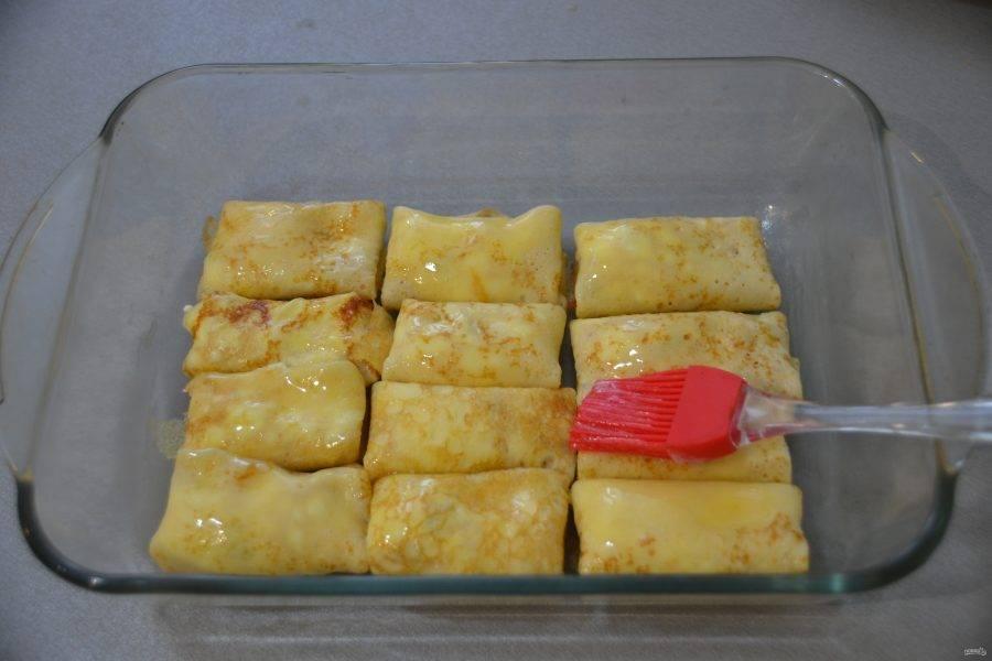 Уложите блинчики первым слоем, смажьте сливочным маслом.
