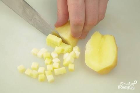 Картофель помойте и отварите до готовности. Почистите и нарежьте его кубиками. Также отварите яйца. Полностью остудите ингредиенты.