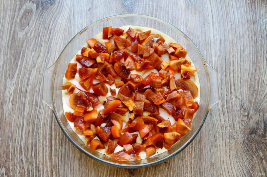 Хурму порежьте на кусочки, удаляя косточки. Разложите поверх яблок по всей поверхности.