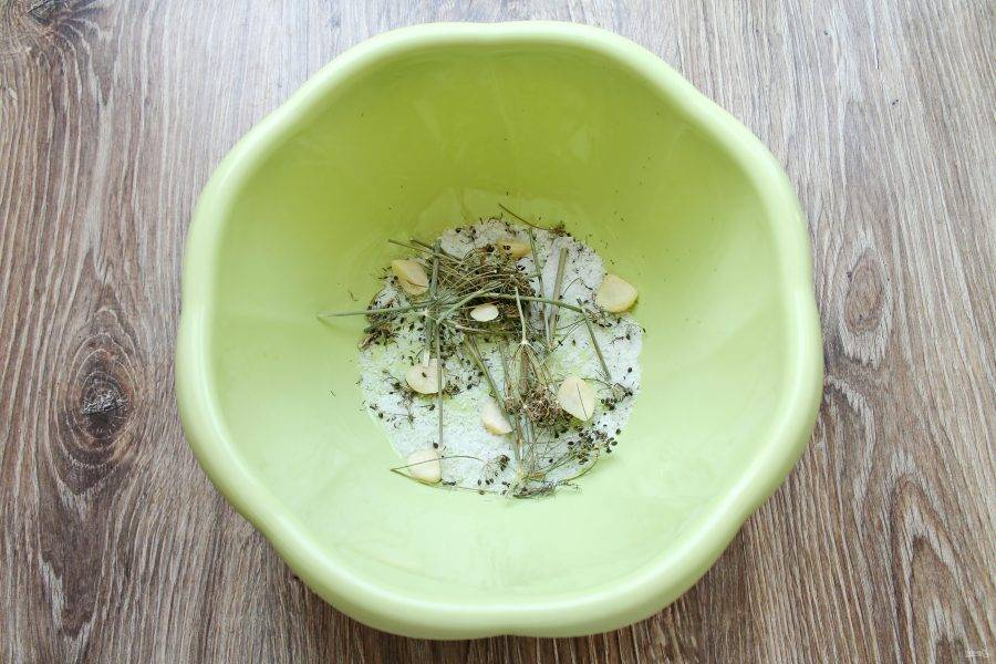 На дно миски насыпьте часть соли, выложите половину укропа и половину очищенного чеснока.