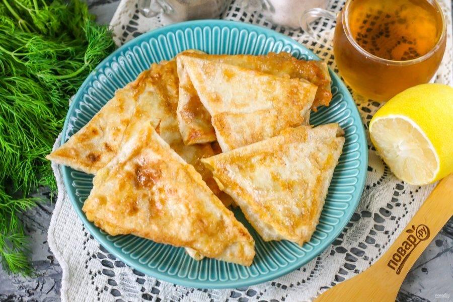 Выложите лаваш с начинкой на тарелку и подайте к столу с чаем или кофе. Блюдо идеально для завтрака или полдника.