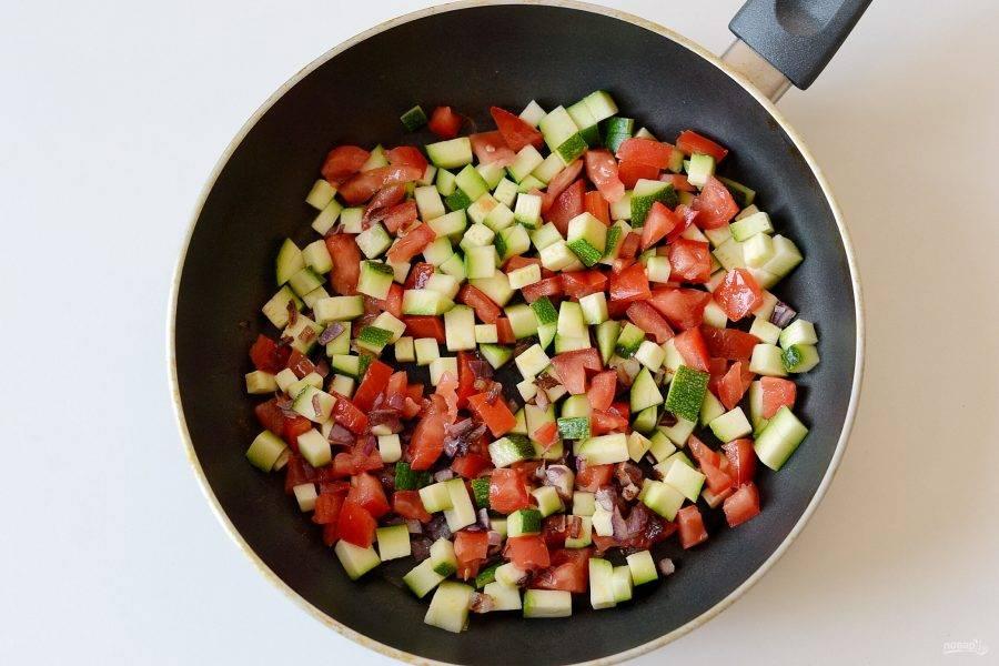 Добавьте цукини и помидор порезанный кубиками. Обжарьте все вместе 6-9 минут, до испарения лишней жидкости. Посолите, поперчите овощи по вкусу и приправьте чесночным порошком.