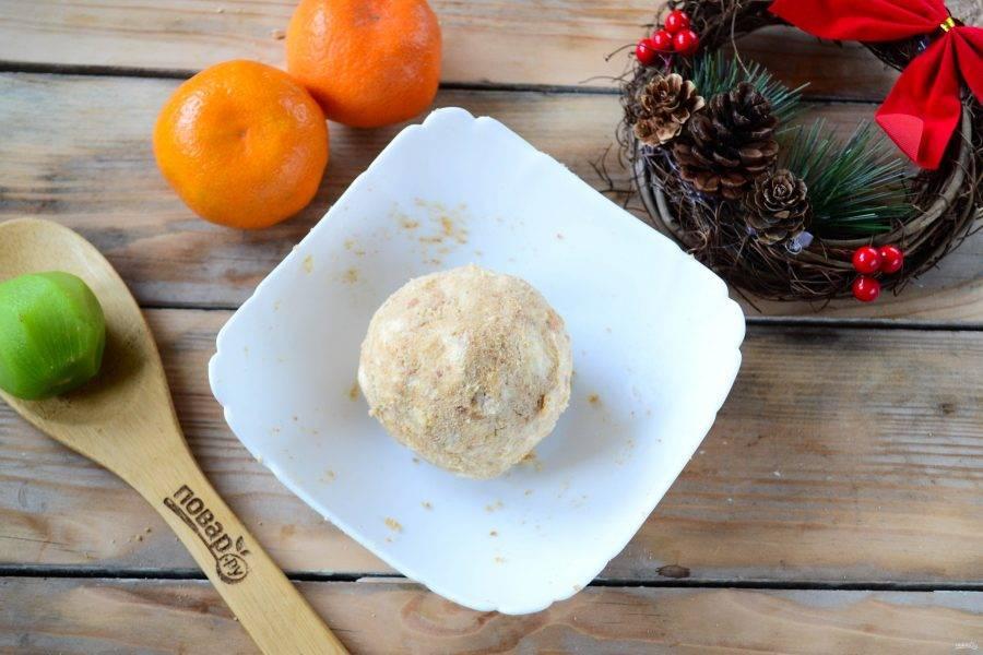 Слегка размягченное сливочное масло порежьте на кусочки и смешайте с измельченным печеньем. Очень быстро все хорошенько перемешайте, чтобы образовался плотный шар. Заверните этот шар в пищевую пленку и отправьте в холодильник на 30 минут.