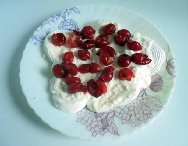 Промываем свежие ягоды вишни и красной смородины. Естественно, подойдут абсолютно любые ягоды и фрукты. Главное, чтобы они сочетались между собой и не резонировали с творожным кремом. Из вишни вытаскиваем косточки. Разделяем зефирины на две части и выкладываем на блюдо в один слой. Одну треть творожного крема вываливаем поверх зефира. Кладем на творог вишню.