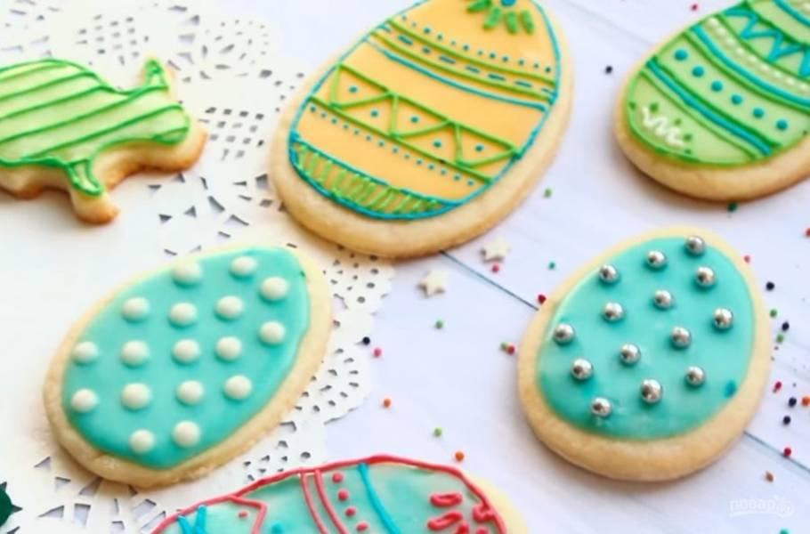 6. Разделите густую глазурь на несколько частей и окрасьте в яркие цвета. С помощью кондитерского мешка украсьте печенье с высохшей глазурью. Приятного аппетита!