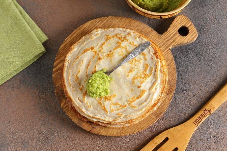 Дайте блинчикам немного остыть, после чего смажьте их тонким слоем пасты из авокадо (около 1-1,5 ч.л. на каждый блин будет достаточно).
