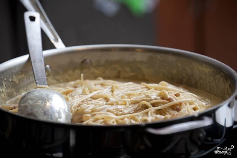 7. Паста к этому времени уже тоже должна быть готова. Выберите ее из кастрюли шумовкой в сковороду к луку и чесноку. Добавьте смесь из сливок и сыра. Огонь поставьте на медленный и перемешайте. Если паста впитает всю жидкость или покажется вам не особенно сочной, добавьте воды, в которой она варилась.