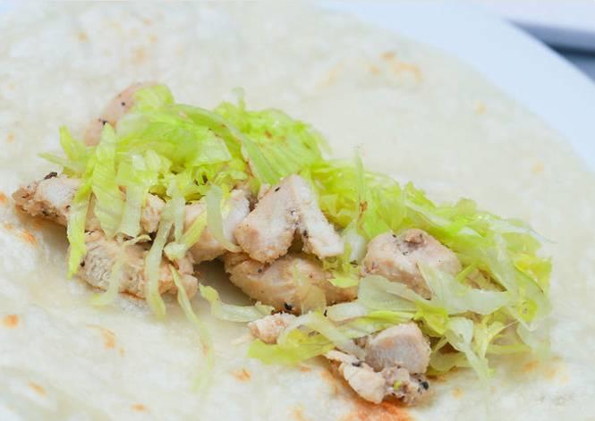 2. Расстилаем лист лаваша, выкладываем кусочки курицы, измельченную капусту и помидор. Можно присыпать специями или взбрызнуть любимым соусом. Сворачиваем тугим рулетом, нарезаем его на рулеты поменьше.