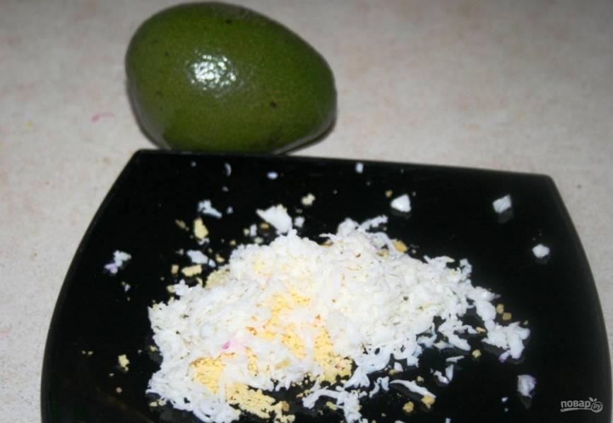 1.Яйца помещаю в миску и заливаю водой, затем отвариваю в течение 7 минут и остужаю, измельчаю яйца на мелкой терке. Авокадо мою, разрезаю на 2 части и вынимаю косточку, мякоть натираю на терке.
