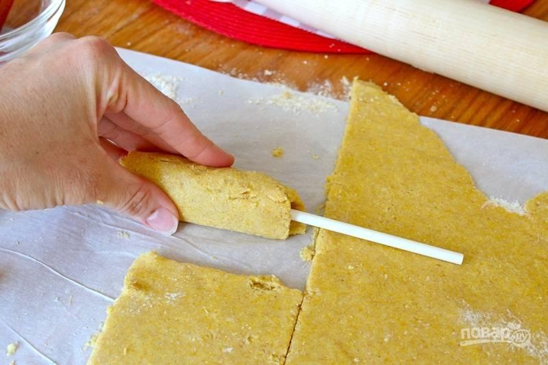 """Сосиски разрежьте на половинки и насадите на деревянные палочки, для каждой сосиски вырежьте по кусочку теста и оберните, чтобы получился плотный """"кокон""""."""