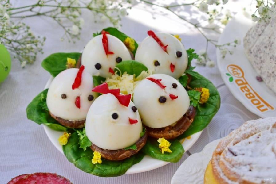 """Яйца очистите, отрежьте нижнюю часть (1 см). Из перца вырежьте гребешки и клювики. Сделайте надрезы на яйцах, соберите головы цыплят, глазки — горошек перца или гвоздика. На блюдо выложите листья шпината, шампиньоны, смажьте их майонезом, украсьте петрушкой. Сверху поставьте """"цыплят""""."""