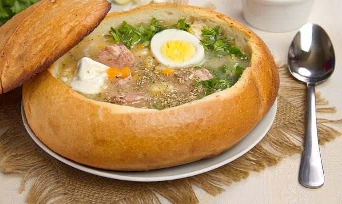 """На стол суп подается в """"хлебной тарелке"""". Для этого срезаем верхушку хлеба и удаляем мякоть. Предварительно можно запечь на 10-15 минут в духовке. Наливаем суп в хлеб, украшаем яйцами, зеленью и сметаной. Приятного аппетита!"""