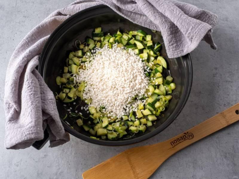 Затем добавьте на сковороду рис, перемешайте и обжарьте около 1 минуты.