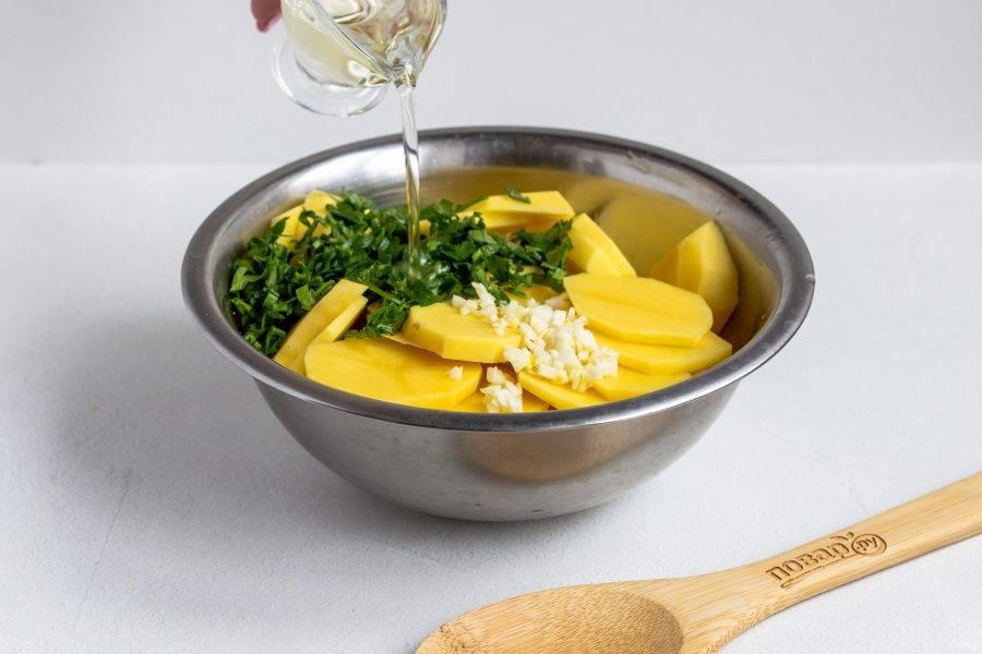 Тем временем займемся картофелем. Нарежьте очищенный картофель кружочками, добавьте рубленные чеснок и зелень. Посолите по вкусу. Залейте растительным маслом и перемешайте.