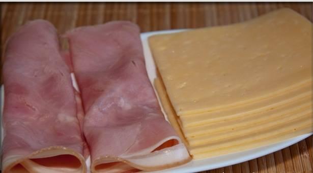 Нарезать сыр и ветчину тонкими пластиками.