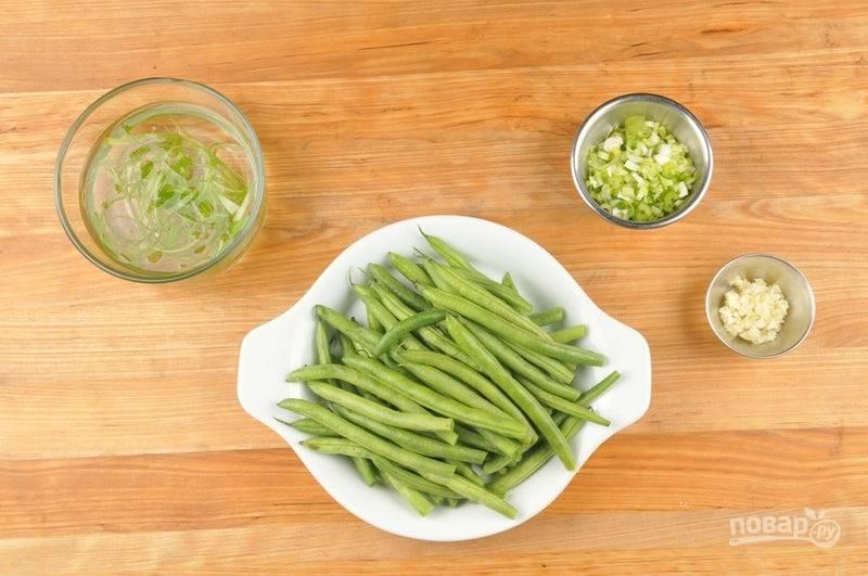 1. Зелёную часть лука нашинкуйте тонкими полосками, затем замочите в холодной воде. Белую часть лука мелко нарубите. Нарежьте фасоль крупными кусочками. Чеснок измельчите.