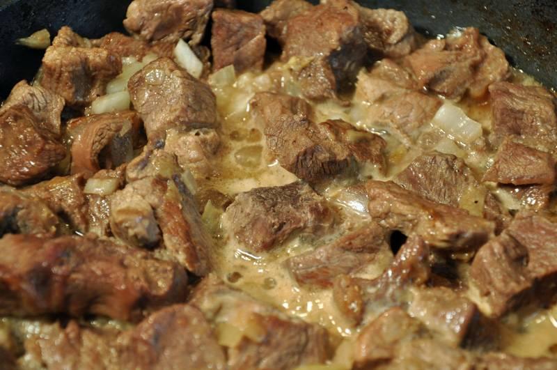 4. Возвращаемся к говядине. Лук надо нарезать кубиками и обжарить на масле в отдельной сковороде, затем добавить к говядине. Под говядиной ставим медленный огонь, добавляем лук, третью часть стакана кипяченой воды или бульона, накрываем крышкой и тушим 1,5 часа.