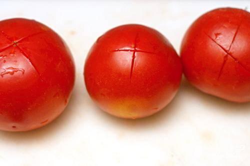 1. В средней кастрюле довести воду до кипения на сильном огне. Сделать крестообразный надрез в нижней части каждого помидора. Разрезайте только кожицу.