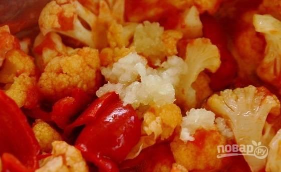 Добавьте в кастрюлю измельчённый чеснок и уксус. Варите салат ещё 5 минут.