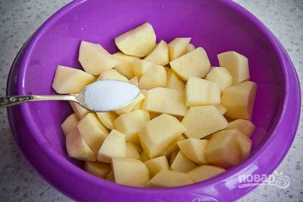 1. Очистите картофель, нарежьте его средними кубиками. Выложите в глубокую мисочку и посолите по вкусу.
