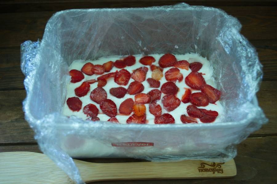 Несколько ягод клубники разрезать пополам и уложить слоем на крем.