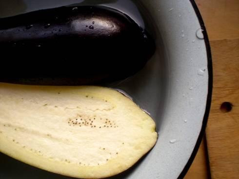 Баклажан помыть, разрезать пополам вдоль и положить в миску с подсоленной водой. Оставить на 30 минут, чтобы убрать горечь из баклажана.