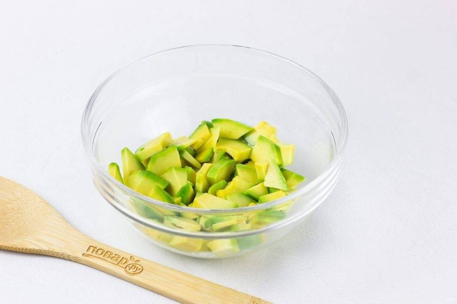 Авокадо очистите от кожицы и косточки, нарежьте произвольно небольшими кусочками. Выложите в миску, сбрызните лимонным соком и перемешайте.