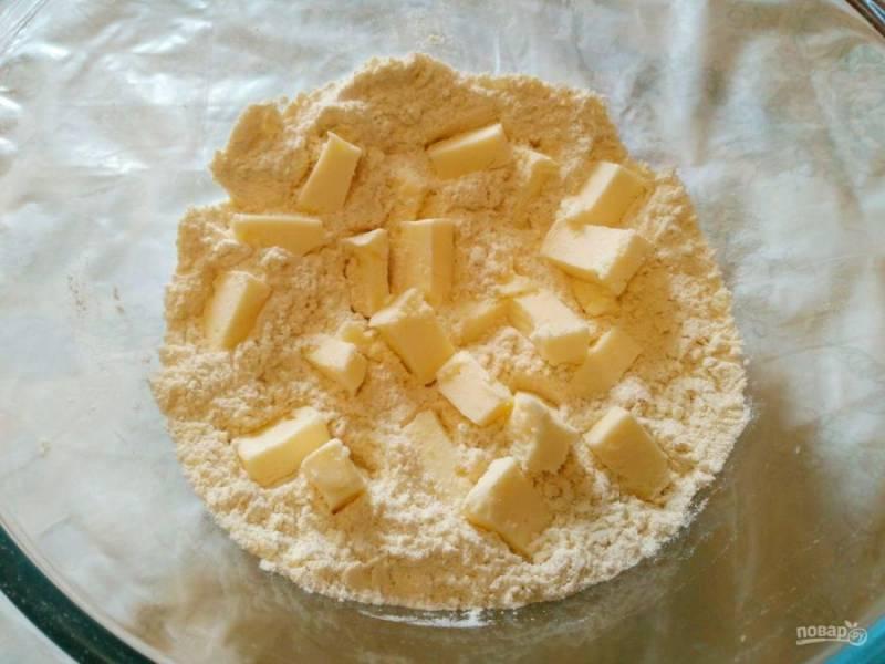 Холодное сливочное масло (пластичное, не замороженное) нарежьте небольшими кубиками и добавьте к сухой смеси.