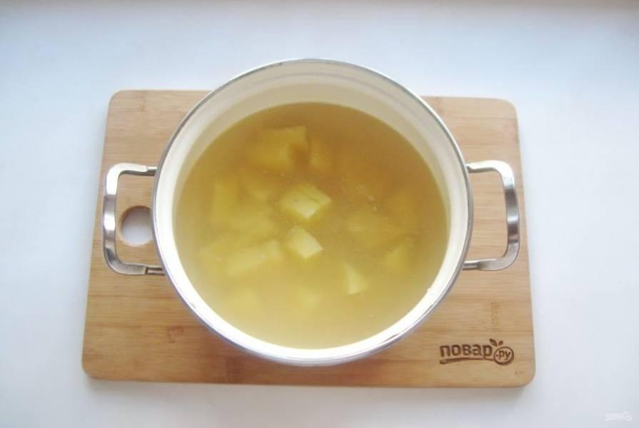 Выложите в кастрюлю нарезанный картофель и залейте его бульоном. Начинайте варить суп.