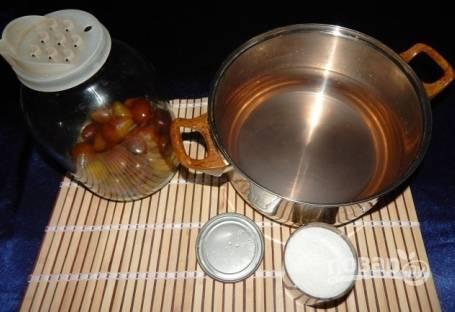 Снова сливаем воду из банки в кастрюлю и добавляем сахар. Хорошо перемешиваем и доводим до кипения. Когда сироп закипел, заливаем в банку и закатываем крышкой.