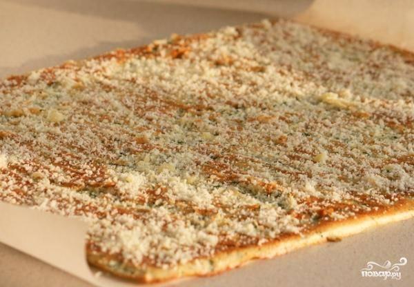 Достаем противень из духовки. Коржу даем остыть, пергаментную бумагу, на которой он выпекался, выбрасываем. Посыпаем корж тертым сыром.