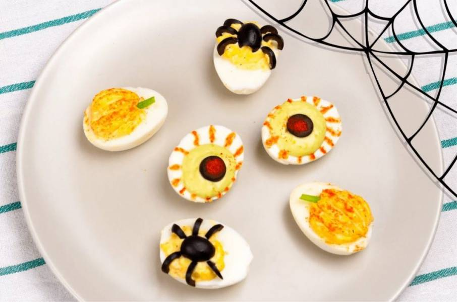 4. Из третьего яйца также выньте желток, смешайте его с соком кинзы (или мякотью авокадо) для получения зеленого цвета. Добавьте майонез, сушеный чеснок и перемешайте. Выложите желток обратно, из маслин сделайте зрачок, а кетчупом нарисуйте прожилки. Приятного аппетита!