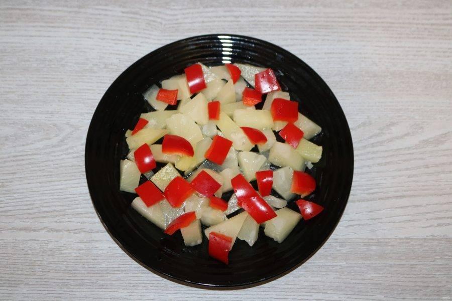 Сладкий перец нарежьте кубиками, выложите на ананас.