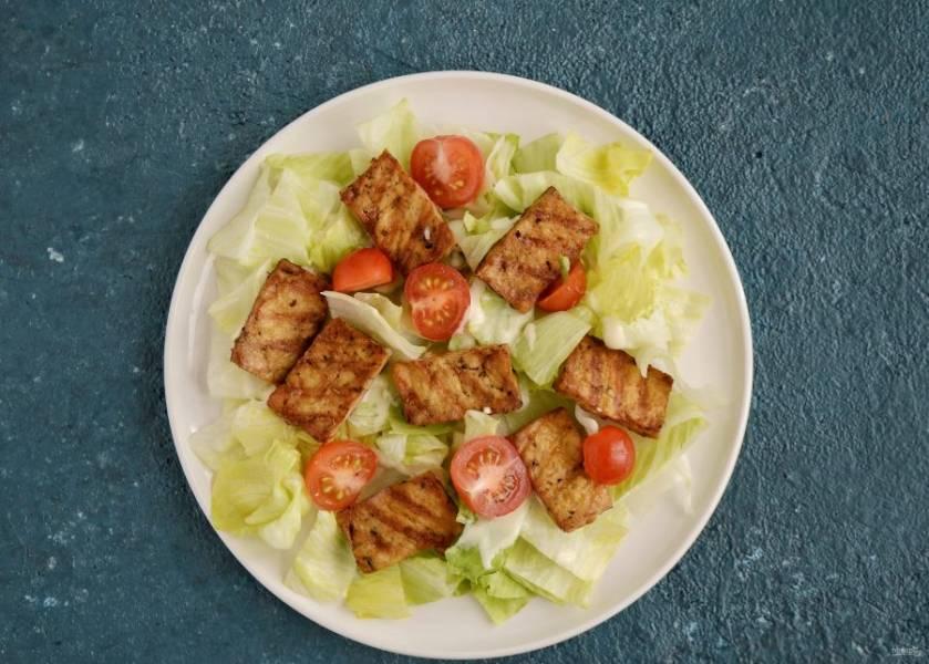 Затем выложите тофу и помидоры черри.